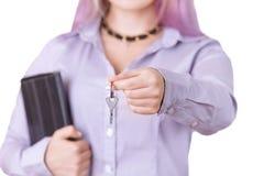 La femme dans une chemise avec un comprimé donne les clés photo stock