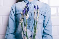 La femme dans une chemise de denim tenant un bouquet des fleurs unblown irisent Photographie stock