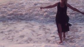 La femme dans une robe noire court à son côté répandant ses bras pour embrasser, sur la mer, de grandes vagues banque de vidéos