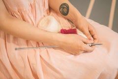 La femme dans une robe rose a mis des aiguilles de tricotage et le tricotage filète sur ses genoux tricotage rêveur méditatif déc Photo stock