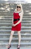 La femme dans une robe rouge sur les étapes en pierre Photos libres de droits