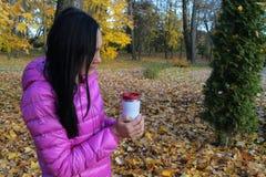 La femme dans la veste lumineuse se tient dans la tasse thermo de mains dans une PA d'automne Images stock