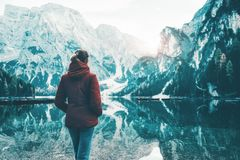 La femme dans la veste rouge se tient sur la côte du lac Braies photo stock