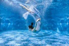 La femme danse sous l'eau image stock