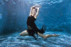 La femme danse sous l'eau dans la piscine photo libre de droits