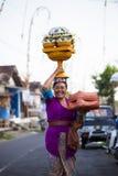 La femme de Balinese avec le cild charge l'offre de la nourriture dans le pot en bois sur sa tête Images stock