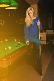 La femme de beauté de charme joue le billard sur la table de billard Image libre de droits