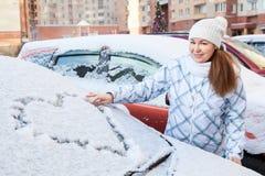 La femme de beauté pendant l'hiver vêtx avec le dessin de coeur sur le pare-brise Image libre de droits
