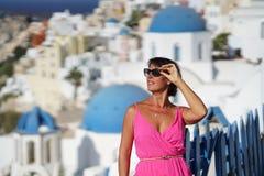 La femme de Beautyful avec la robe fuchsia admire le paysage d'Oia dans Santorini photo stock