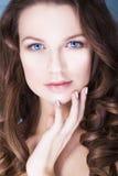 La femme de brune avec des yeux bleus sans composent, peau et mains impeccables naturelles près de son visage Image stock