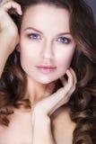 La femme de brune avec des yeux bleus sans composent, peau et mains impeccables naturelles près de son visage Images libres de droits