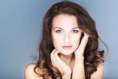 La femme de brune avec des yeux bleus sans composent, peau et mains impeccables naturelles près de son visage Photos stock
