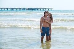 La femme de brune dans le bikini étreint un bel homme aux cheveux longs par derrière, se tenant en mer Photos libres de droits