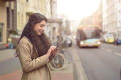 La femme de brune des textes lit son téléphone et sourit photographie stock libre de droits