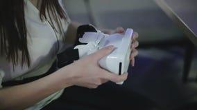 La femme de brune insère le téléphone portable dans des verres d'une réalité virtuelle, et met dessus sa tête banque de vidéos
