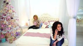 La femme de brune secrètement de l'ami commande le cadeau, chuchote au téléphone, se reposant sur le lit dans la chambre à couche banque de vidéos
