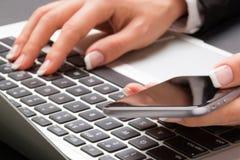 La femme de bureau dactylographie sur l'ordinateur portable et tient le smartphone Images libres de droits