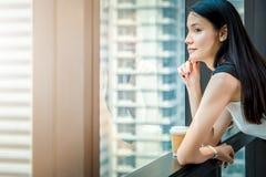 La femme de bureau font une pause du travail au stand près de la fenêtre avec prendre le café photographie stock