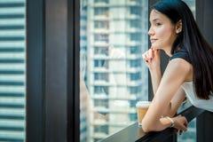 La femme de bureau font une pause du travail au stand pr?s de la fen?tre avec prendre le caf? images stock