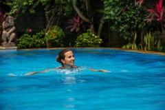 La femme de Caucasican se repose dans la piscine bleue dans les tropiques Images stock
