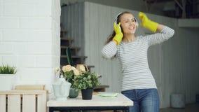 La femme de charge drôle de jeune femme attirante a l'amusement pendant faire le ménage, la jeune dame est chantante et dansante  banque de vidéos