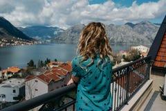 La femme de cheveux assez blonds apprécie la vue de la mer et de la montagne Photos stock