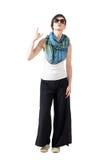 La femme de cheveux courts avec des lunettes de soleil et l'écharpe montrant des klaxons de diable remettent le signe Images libres de droits