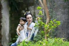 La femme de classique chinois dans la robe de Hanfu apprécient le temps gratuit avec le bébé et les amis intimes Photographie stock