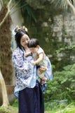 La femme de classique chinois dans la robe de Hanfu apprécient le temps gratuit avec le bébé et les amis intimes Image libre de droits
