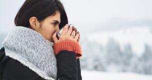 La femme de congélation boit du thé chaud au milieu de la montagne, dans un jour de congélation avec la boisson de jeune femme de clips vidéos
