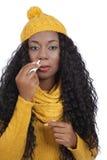La femme de couleur applique la pulvérisation nasale Photographie stock libre de droits