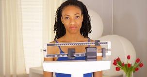 La femme de couleur déçue vérifie le poids et marche loin Photo libre de droits