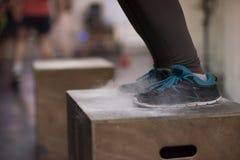 La femme de couleur exécute des sauts de boîte au gymnase Photo stock