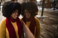 La femme de couleur heureuse se tient sur la rue à côté de sa réflexion dans la fenêtre photos stock