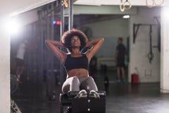 La femme de couleur que faire se reposent se lève au gymnase photos stock