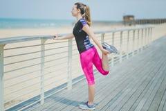 La femme de coureur étirant des jambes avec la jambe d'exercice d'étendue de tendon de mouvement brusque s'étire Athlète féminin  Photos stock