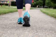 La femme de coureur courant sur une route étroite, se ferment sur la chaussure/mouchard Photo stock