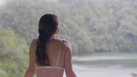 La femme de déplacement appréciant le paysage de lac parmi les collines vertes a couvert la fille de touristes de forêt tropicale banque de vidéos
