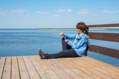 La femme de détente s'assied sur un pilier en bois avec le comprimé Photo libre de droits