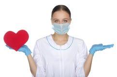 La femme de docteur dans le masque pèse en main le coeur Image libre de droits
