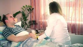 La femme de docteur lui donnent les pilules masculines de drogues de patient banque de vidéos