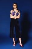 La femme de fantaisie dans le bleu a plissé le pantalon et le dessus floral Photo libre de droits