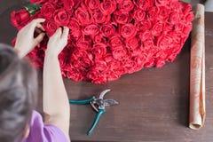 La femme de fleuriste prépare un grand bouquet des roses rouges Image stock