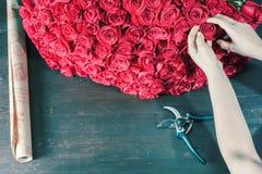 La femme de fleuriste prépare un grand bouquet des roses rouges Images stock