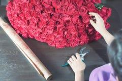 La femme de fleuriste prépare un grand bouquet des roses rouges Photo stock