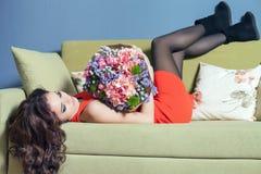 La femme de fleuriste prépare un grand bouquet des roses rouges Photo libre de droits