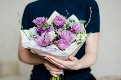 La femme de fleuriste tenant un beau bouquet de floraison coloré de fleur des tulipes roses blanches fraîches, ranunculus, part d photographie stock