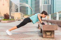 La femme de forme physique faisant des pieds a élevé des pousées sur un banc dans la ville Fille sportive s'exerçant dehors Photos stock