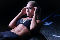 La femme de forme physique faisant l'ab craque sur une boule de gymnase Photographie stock libre de droits