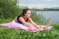 La femme de forme physique s'étirant de retour, jambe de tendon muscles la courbure en avant posée Photo libre de droits